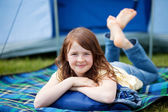 Girl Lying On Blanket With Tent In Background — Stock Photo