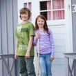 Stock Photo: Siblings Standing Together At Entrance Of Camping Houses