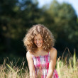 Smiling girl walking through tall grass — Stock Photo