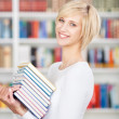 Young Woman Carrying Stacked Books In Library — Stock Photo