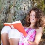 ragazza leggendo il libro mentre appoggiato su un tronco d'albero — Foto Stock #26005571