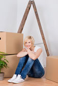 Young Woman With Cardboard Boxes Sitting On Hardwood Floor — Stockfoto