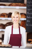 Young saleswoman working in bakery — Stock Photo