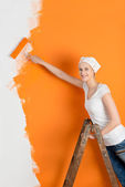 Young Woman Painting Wall With Roller In House — Stock Photo