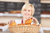 Waitress Arranging Breads In Basket At Cafe — Stock Photo