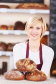 Sonriente vendedora trabajando en la panadería — Foto de Stock