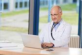 доктор с рук на подбородке и ноутбук на стол — Стоковое фото