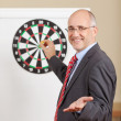 Businessman Gesturing While Holding Dart Attached To Target On F — Stock Photo