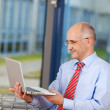 Mature Businessman Holding Laptop — Stock Photo