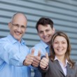 Businesspeople Gesturing Thumbs Up Against Shutter — Stok fotoğraf