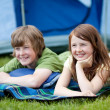 Two Kids Lying On Blanket With Tent In Background — Stock Photo