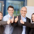 Businesspeople Showing Thumbs Up Sign In Office — Stock Photo #26012821