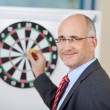 Businessman Attaching Dart On Target In Office — Stock Photo