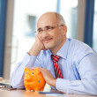 Businessman With Piggybank Looking Away At Desk — Stock Photo