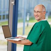 Mature Surgeon Holding Laptop — Stock Photo