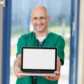 Leende kirurg hålla laptop i kliniken — Stockfoto
