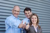 Företagare gestikulerande tummen upp mot slutare — Stockfoto