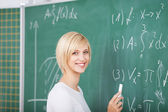 Female Student Solving Sums On Chalkboard In Classroom — Stock Photo