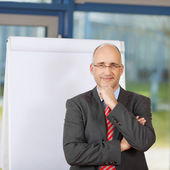 Mature Businessman With Arm On Chin By Flipchart — Stock Photo