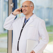 доктор с помощью мобильного телефона, удерживая ноутбук — Стоковое фото