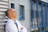 доктор, опираясь на стене во время глядя — Стоковое фото