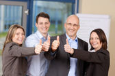 Businesspeople Showing Thumbs Up Sign In Office — Stock Photo