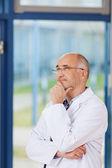 Médico con la mano en la barbilla apartar la mirada — Foto de Stock