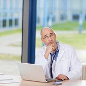 Doordachte arts met laptop op bureau — Stockfoto