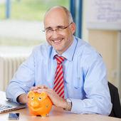 Confident Businessman With Piggybank At Desk — Stock Photo