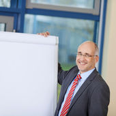Mature Businessman Standing By Flipchart — Stock Photo