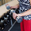 Young woman using dumbbells in a gym — Stock Photo