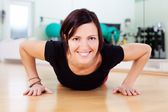 Woman doing push-ups in a gym — Stock Photo