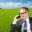 Stock Photo: Businessmusing his mobile in countryside