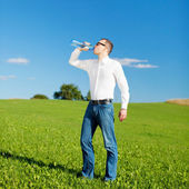 Man drinking bottled water in a field — Stock Photo