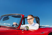 Smiling man driving a red cabriolet — Stock Photo