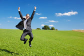 Excited businessman jumps high in the air — Stockfoto