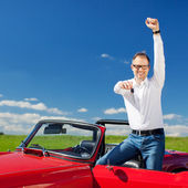 Excited man celebrating ownership of a cabriolet — Stock Photo