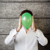 Businessman Holding Balloon In Front Of Face Against Wooden Wall — Stock Photo