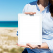 Woman showing white paper by the beach — Stock Photo