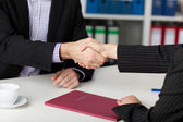 Businesspeople Shaking Hands At Office Desk — Stock Photo