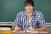 Male Student With Binder Sitting At Desk — Stock Photo