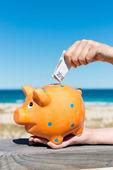 Womans Hand Inserting Euro Note In Piggybank At Beach — Stock Photo