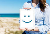 Woman Displaying Digital Tablet With Smiley Face At Beach — Stock Photo