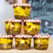 Jars of white cheese cubes and herbs in a grocery — Stock Photo #26073301