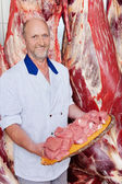 Butcher holding a tray full of chopped raw meat — Stock Photo