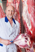 Butcher holding a big lump of raw meat — Stock Photo