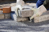 Construction worker paving the brick road — Stock Photo