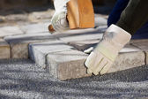 Construction worker fixing a brick road — Stock Photo