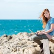 Smiling woman sending emails at the seaside — Stock Photo