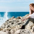 Thoughtful woman relaxing at the sea — Stock Photo #26088383